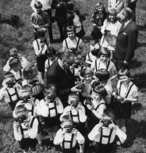 """Die jungen Bewohner des Kinderheims in Fót/Ungarn 1972 mit ihren neuen """"Pajtás"""" (Kumpel) Kameras. Die Geräte waren ein Geschenk der Forte-Fabrik, des Nachfolgers der ungarischen Kodak-Fabrik in Vác. Die Produktionsstätte, die den mittelosteuropäischen Markt mit Kodak Produkten versorgen sollte, wurde bereits 1912 gegründet. Wegen des Ersten Weltkriegs konnte sie jedoch ihre Arbeit erst 1922 aufnehmen. Nach der Verstaatlichung 1948 trug die Fabrik den Namen """"Forte"""" und stellte v.a. Fotopapier und Filme für den Export sowie den ungarischen Markt her. Auf dem Bild sind rechts im Hintergrund der Gründungsdirektor des Kinderheims, Dr. Lajos Barna, und ein Vertreter der Forte-Fabrik zu sehen."""