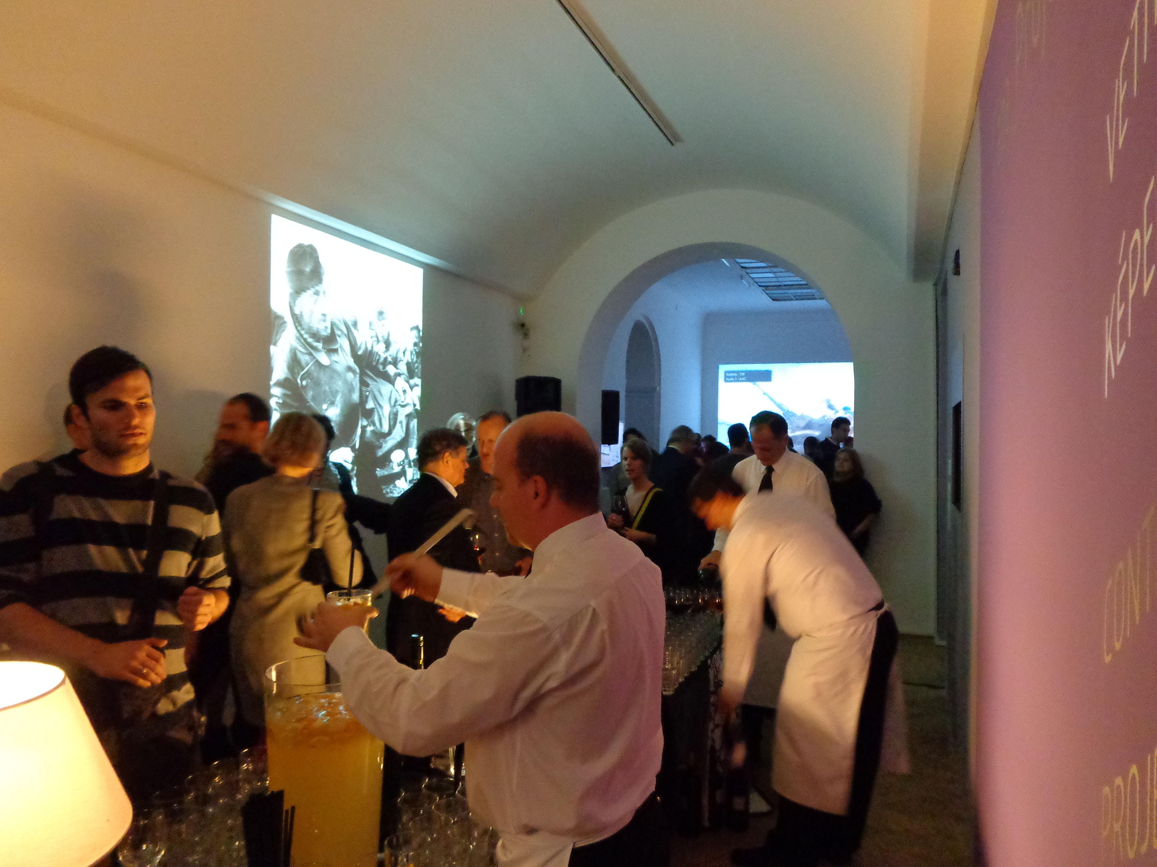 """Einer der Ausstellungsräume während der Eröffnungsfeier. Links im Bild ist """"Robert Capa's Masterworks – Politically Correct and Censored Edition"""", der Beitrag von István Szőnyi, zu sehen."""