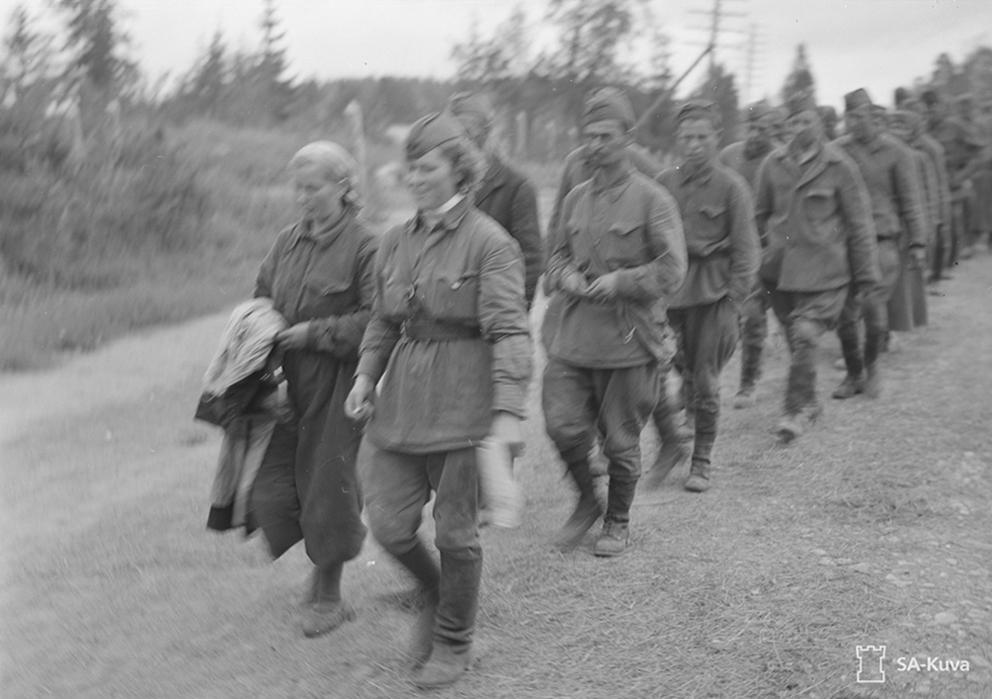 """Ein finnisches PK-Foto von PK-Fotograf Manninen, aufgenommen in der Nähe von Sortavala im August 1941. Laut Bildunterschrift zeigt das Bild sowjetische Gefangene. Vorne sind zwei Soldatinnen zu erkennen, die nicht dem deutschen Feindbild von blutrünstigen """"Flintenweibern"""" entsprachen. Das Bild ist, vielleicht auch wegen der Unschärfe, von der Zensur als """"nicht zu veröffentlichen"""" klassifiziert. Quelle: Finnish Wartime Photograph Archive (CC)"""