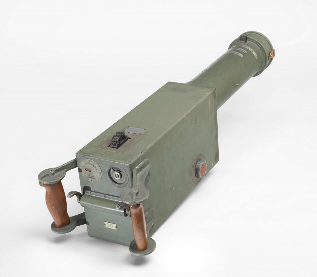 """Die """"Maschinengewehrkamera"""" wurde im Ersten Weltkrieg von Oskar Messter (1866-1943) entwickelt und von der Firma Ernemann in Dresden gebaut. Vorbild war das reale Maschinengewehr MG 08. Die Handgriffe des Abzugs waren identisch, ebenso die Visiereinrichtung. Statt eines Patronengürtels enthielt die Kamera einen Filmstreifen."""