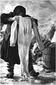 Eine rumänische Frau wäscht die Wäsche ihrer Familie im Eisloch. (Desești, Rumänien,1973)
