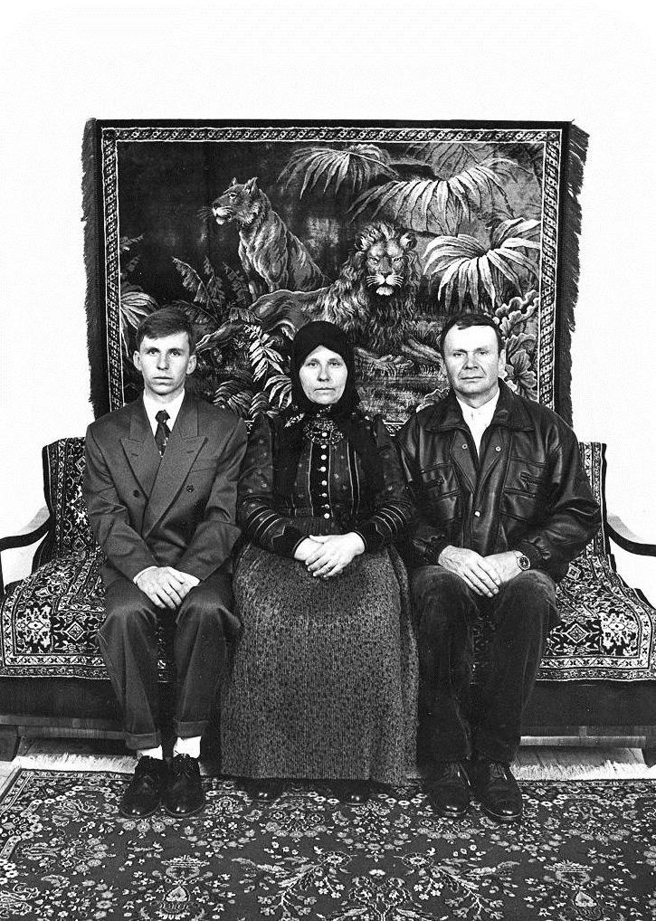 """Familienporträt aus dem Jahr 1997: Der Ehemann, die Ehefrau und ihr Sohn posieren in der """"guten Stube"""" ihres Hauses. Die Kleidung der Männer und der neue Wandteppich im Hintergrund weisen auf die Verdrängung des traditionellen, dörflichen Lebensstils hin. (Szék/Sic, Rumänien, 1997)"""
