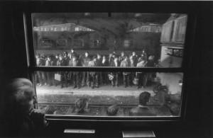 Bahnhof Miskolc: Menschen warten auf dem Bahnsteig auf die Einfahrt eines Arbeiterzuges. Links unten im Bild ist András Skarbit, die Hauptfigur der zwischen 1978 und 1988 erstellten Fotoreihe, zu sehen.