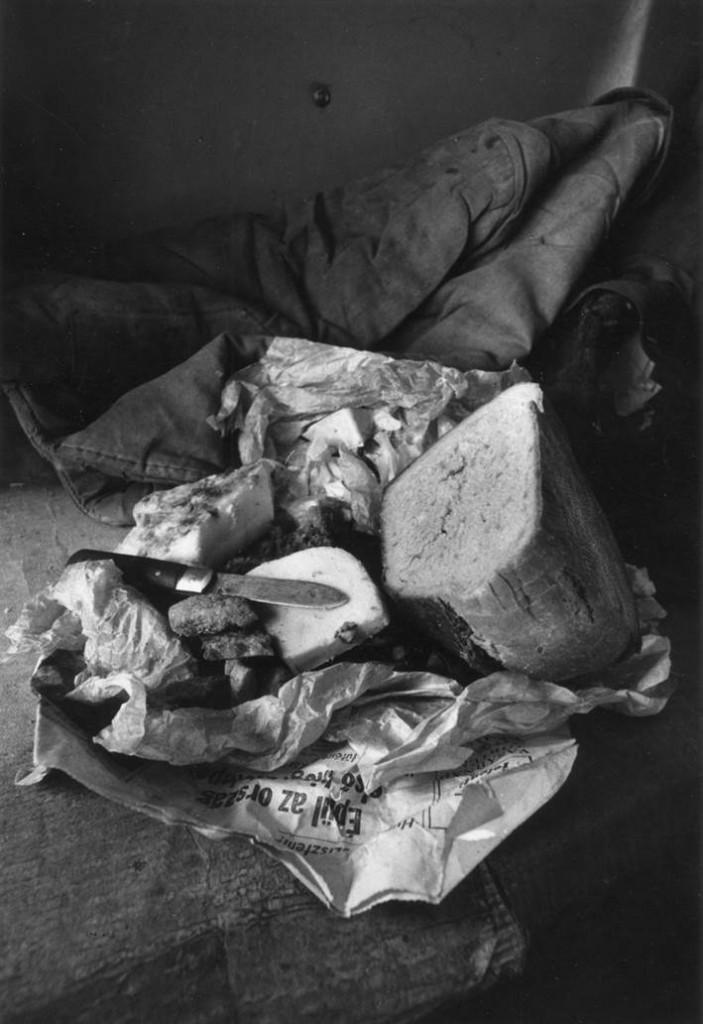 """Das von zu Hause aus mitgebrachte Essen (Brot, Speck, kolbász usw.) wickelten die Arbeiter in Zeitungspapier ein. Der Titel des Artikels lautet: """"Épül az ország!"""" [Das Land wird aufgebaut!]"""