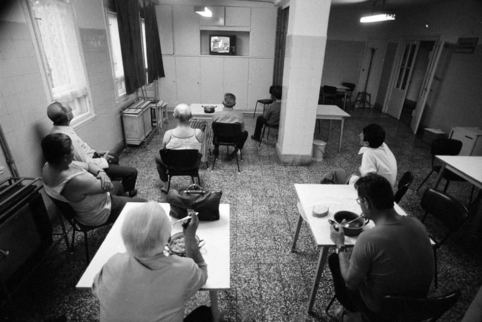 Beim Abendessen im Gemeinschaftsraum des Arbeiterwohnheims essen die Männer - jeder für sich - aus dem eigenen Topf. Nebenbei wird ferngeschaut.