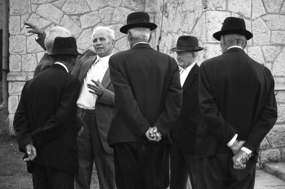 An einem Sonntag, nach der Messe: Die Älteren im Dorf unterhalten sich mit Skarbit. Sie hören ihm zu, während er über die Hauptstadt Budapest berichtet.
