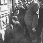 """Im Zuge der nach dem """"Anschluss"""" Österreichs einsetzenden Pogrome werden jüdische ÖsterreicherInnen wie etwa dieser Teenager zu antisemitischen Beschmierungen gezwungen. Klar erkennbar in dieser mit der Zeit zum Schlüsselbild des Antisemitismus' mutierten Aufnahme ist die voyeuristische Beteiligung der Bevölkerung, die aber in den jeweiligen Untertiteln meist nicht thematisiert wird."""