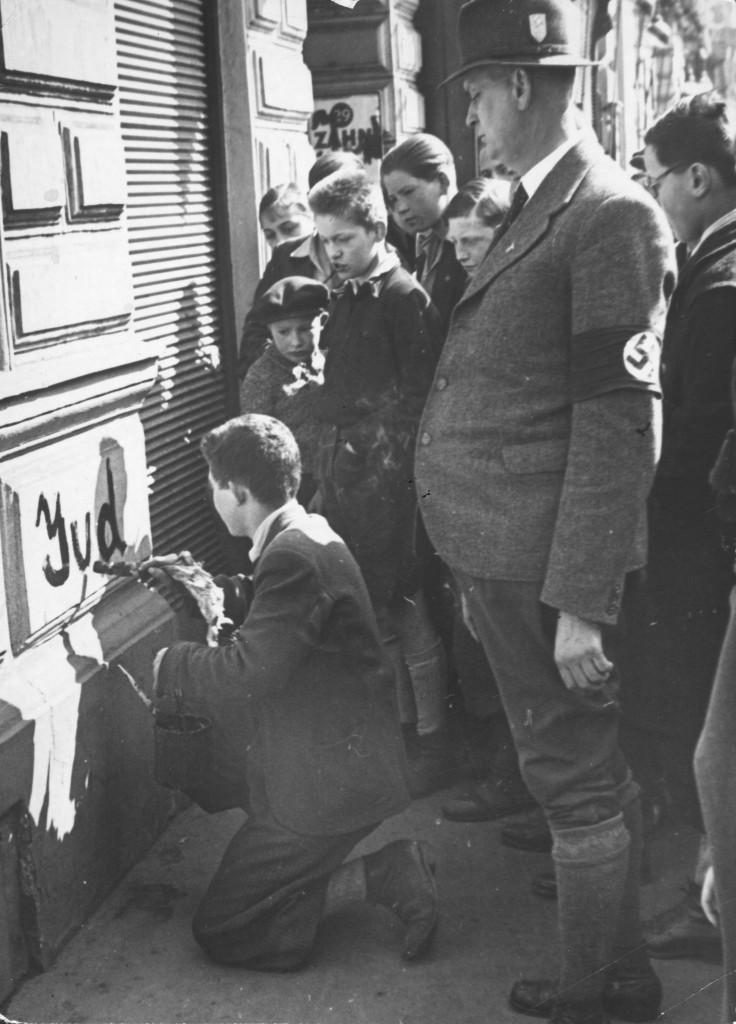 """Im Zuge der nach dem """"Anschluss"""" Österreichs einsetzenden Pogrome werden jüdische ÖsterreicherInnen wie etwa dieser Teenager zu antisemitischen Beschmierungen gezwungen. Klar erkennbar ist in dieser mittlerweile zum Schlüsselbild des Antisemitismus avancierten Aufnahme die voyeuristische Beteiligung der Bevölkerung, die aber in den jeweiligen Untertiteln meist nicht thematisiert wird."""