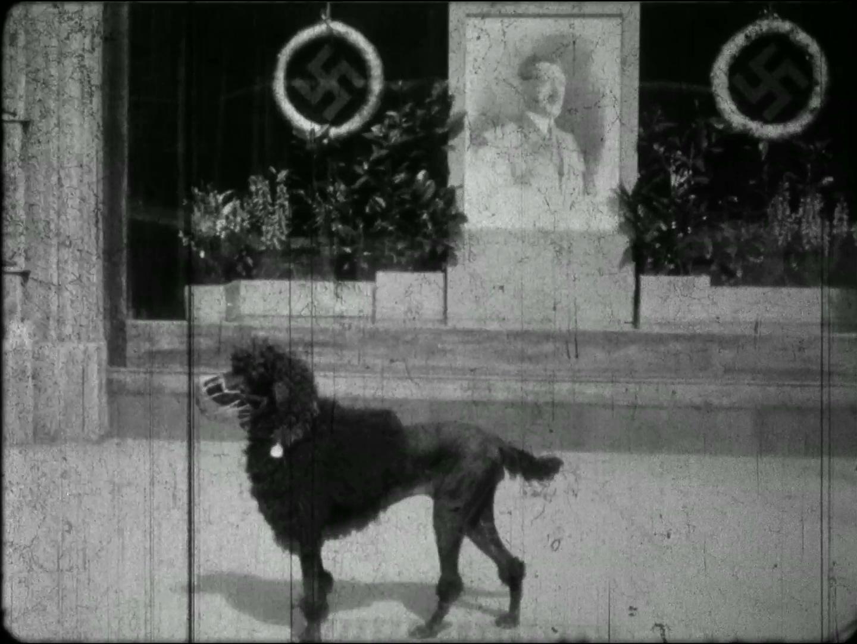 "Filmstill: Vor einem ""Hitleraltar"" (Loos-Haus am Michaelerplatz): AMFilmstill: Vor einem ""Hitleraltar"" (Loos-Haus am Michaelerplatz): AMATEURAUFNAHMEN WIEN, FRÜHJAHR 1938 (ÖFM) http://stadtfilm-wien.at/film/104/"