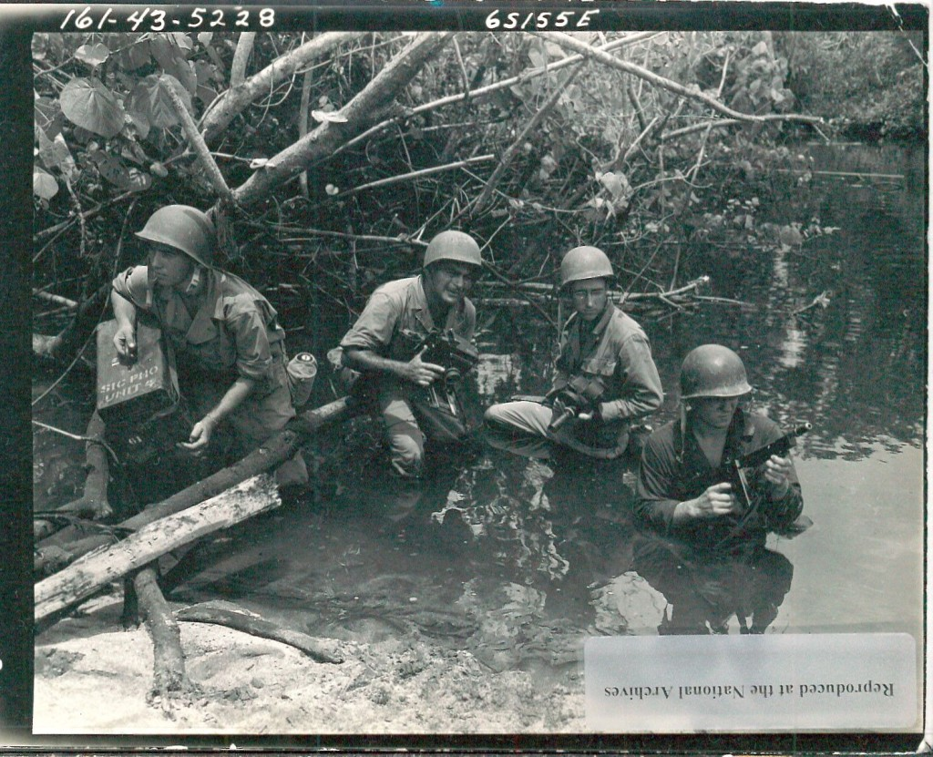 Abb. 2: Members of the U.S. Army Photographic Unit on Bougainville going through water and mud on a photographic mission, 28 Nov 1943, National Archives Washington, 111-SC-Box_802, Album 6217