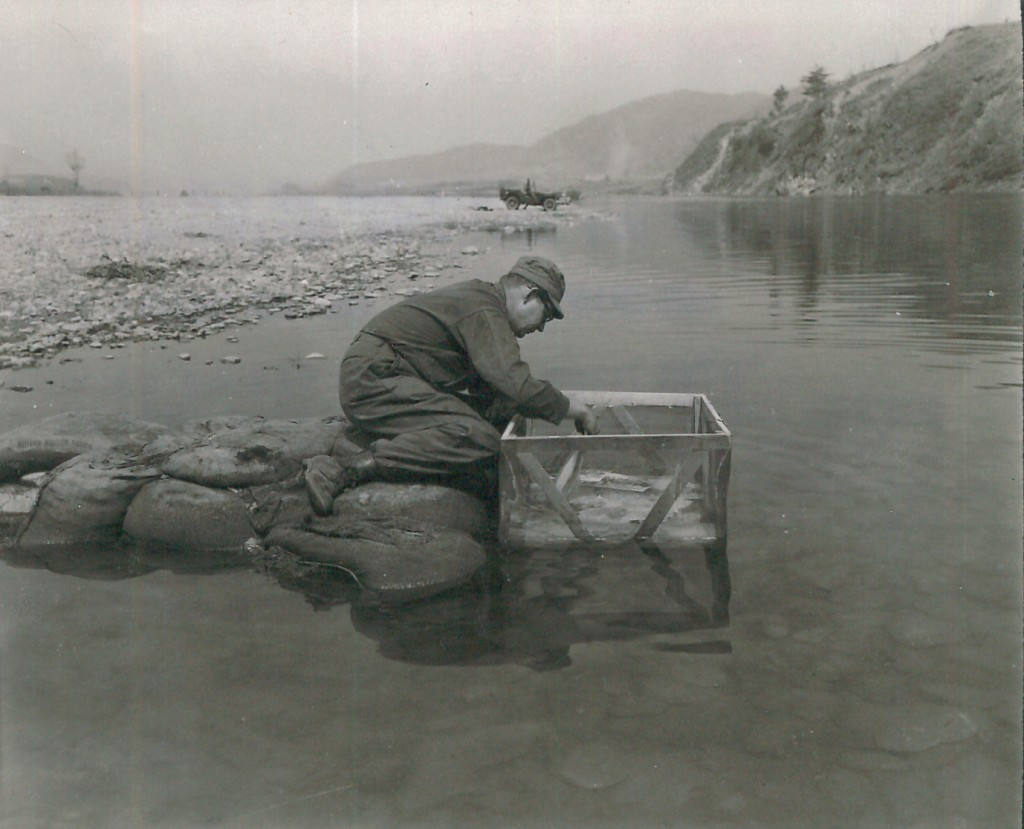 Abb. 3: A laboratory technician of the 4th Sig Bn Corps 8th Bat washes prints in the Hongomon-Gang river in Korea using a fine weave screen basket. The sandbag pier was constructed in order to reach water of sufficient depth and rate of flow to wash prints properly. No other means of washing prints properly. US Army photograph by CPL C.E. Abrahamson, 18 April 1951, National Archives Washington, 111-SC-364984