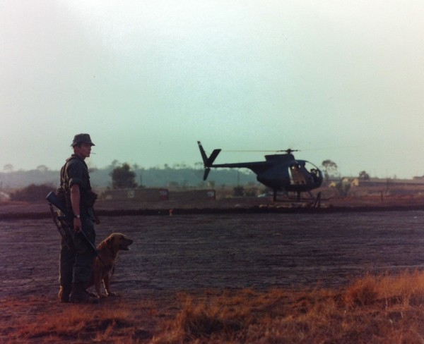 Abb. 8: Vietnam: A dog handler (...) and his dog wait at a helipad for an early evening flight to a combat area, Official U.S. Army Photo (Releases), National Archives Washington, 111-CCV-459E