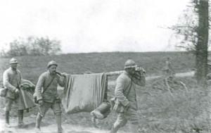 Drei Soldaten transportieren einen weiteren Soldaten auf einer Behelfstrage. Aus dem Buch von Ulrich Hägele: Walter Kleinfeldt: Fotos von der Front 1915-1918, S. 172 © Waxmann Verlag