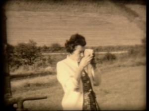 Filmstill einer Frau mit Schmalfilmkamera. Aus dem  Filmarchiv des LWL-Medienzentrums für Westfalen, Bestand Schönert-Bischopink, Arnsberg (1950er)