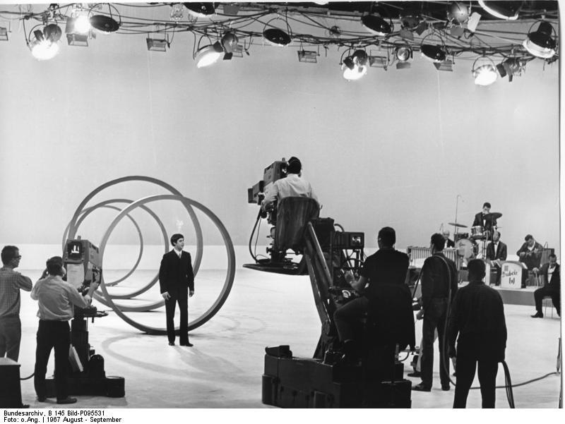 """Berlin-West: 25. Große Deutsche Funkaustellung 1967 in Berlin: Proben zur Farbfernsehveranstaltung. """"Show ist Show"""" aus der Deutschlandhalle, Berlin 1967, Fotograf unbekannt, Presse- und Informationsamt der Bundesregierung - Bildbestand (B 145 Bild), Quelle: Wikimedia Commons / Bundesarchiv, B 145 Bild-P095531. Lizenz: CC-BY-SA 3.0 https://commons.wikimedia.org/wiki/File:Bundesarchiv_B_145_Bild-P095531,_Berlin,_Funkausstellung,_Proben_f%C3%BCr_Fernsehshow.jpg https://creativecommons.org/licenses/by-sa/3.0/de/deed.en"""
