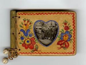 """Kordelgebundenes Steckalbum mit herzförmig ausgesägtem Holzeinband. Auf der Rückseite des Fotos findet sich der handschriftliche Vermerk """"Hamburg"""". Format: 7 x 11 cm, 20 Seiten, Fotos: 6 x 6 cm, Fotopapier: Agfa-Lupex. Quelle: Sammlung Ulrich Prehn"""