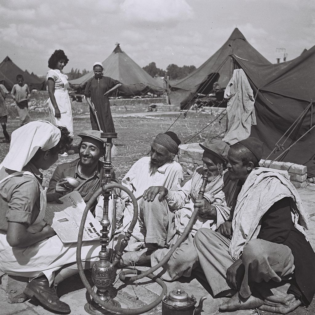 Zoltan Kluger (Foto): A young Yemenite nurse reading from a newspaper to new migrants at the Rosh Ha'ayin camp. Israeli National Photo Archive, 01.10.1949 Quelle: https://commons.wikimedia.org/wiki/File%3AYemenites_at_Rosh_Haayin.jpg Lizenz: Public domain