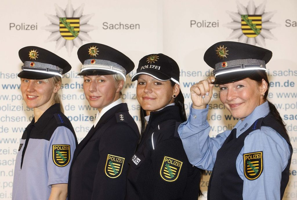 Uniform der Polizei der Länder Berlin, Brandenburg und Sachsen 2009. Fotograf: unbekannt, 4. November 2009. Quelle: Sächsisches Staatsministerium des Innern / Wikimedia Commons https://commons.wikimedia.org/wiki/File:Uniformmodell_Brandenburg2.jpg?uselang=de, Lizenz: CC BY-SA 3.0 https://creativecommons.org/licenses/by-sa/3.0/deed.de